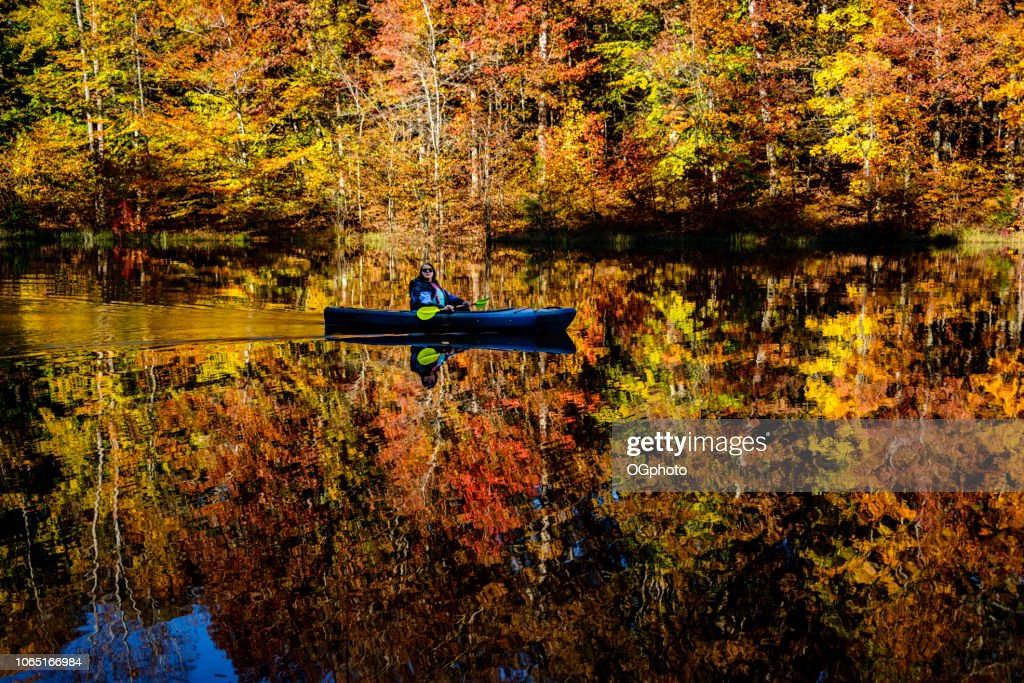 Woman kayaking in lake reflecting the autumn colors : Stock Photo
