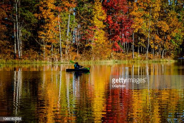 Woman kayaking in lake reflecting the autumn colors