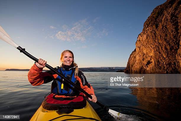 Woman kayaking in still lake