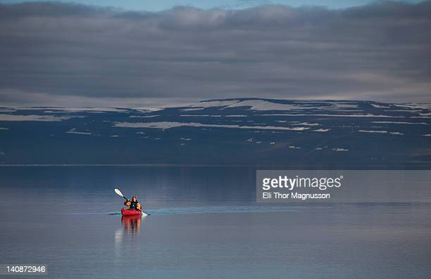 woman kayaking in still lake - westfjords iceland stock photos and pictures