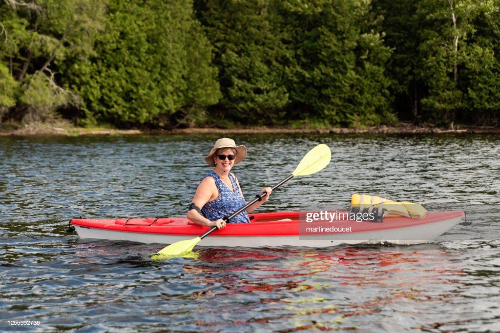 50 + woman kayaking on a lake. : Stock Photo