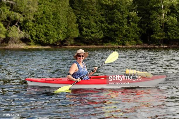 """50 + kvinna kajakpaddling på en sjö. - """"martine doucet"""" or martinedoucet bildbanksfoton och bilder"""