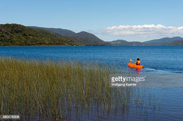 Woman kayaking on Lake Cucao in Cucao Chiloe National Park on Chiloe Island Chile
