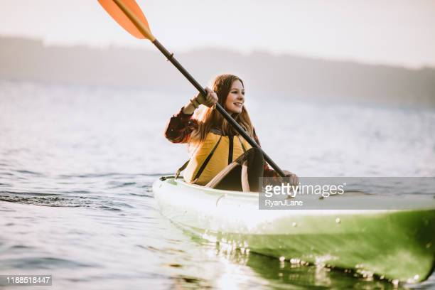 woman kayaking on pacific northwest adventure in the puget sound - puget sound stock pictures, royalty-free photos & images