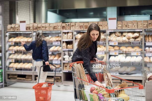 Woman keeping bananas in shopping cart against rack at supermarket