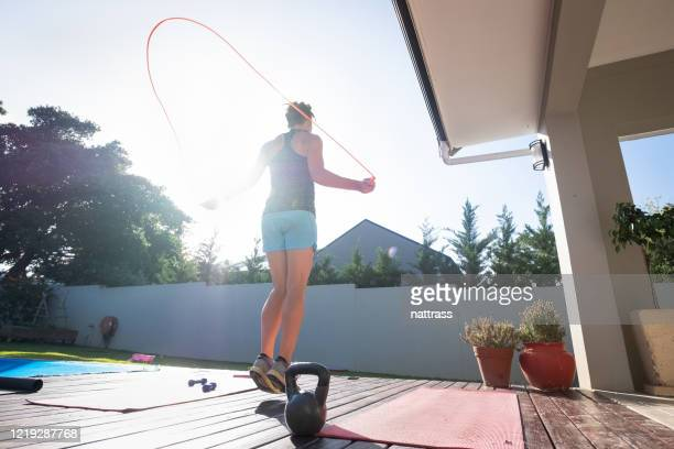 woman keeping fit by doing some jump rope - skipping along stock pictures, royalty-free photos & images