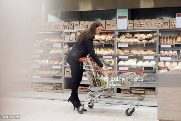 Woman keeping paper bag in shopping cart while standing by bread rack at supermarket