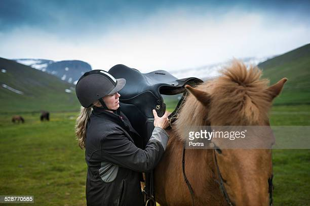 Woman keeping saddle on horse at field