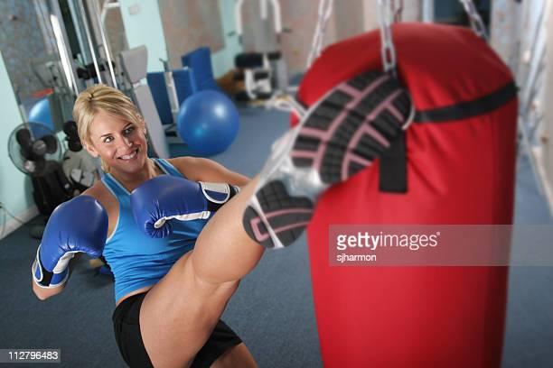 woman kicking punching bag in gym exercising