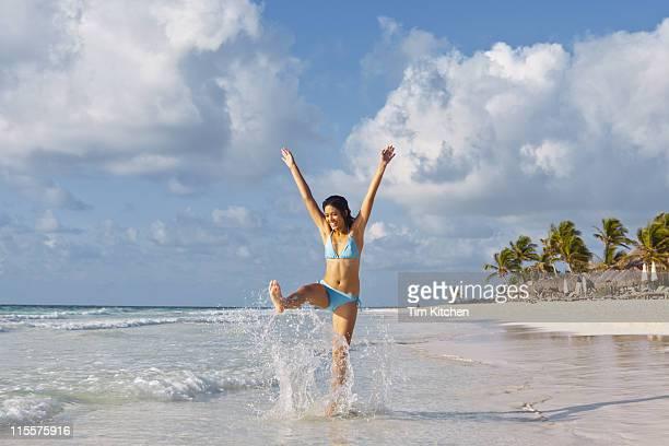 woman kicking surf on tropical beach, smiling - chutar imagens e fotografias de stock