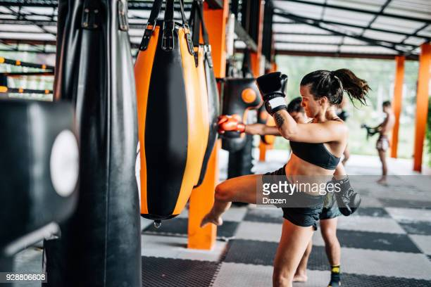 woman kicking the punching bag - mixed martial arts stock pictures, royalty-free photos & images