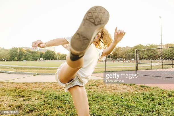 Woman kicking up leg on sports field
