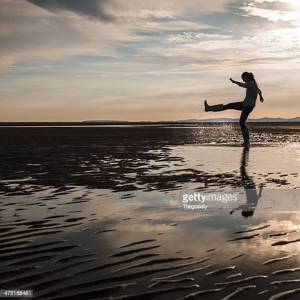 UK, junge Frau Entspannung im Wasser am Strand