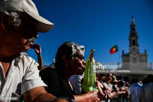 A woman kiss a figure of Our Lady Fatima during the procession at the Fatima shrine in Fatima central Portugal on May 13 2019 Thousands of pilgrims...
