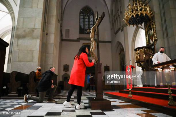 Woman kisses a figure of Jesus Christ inside St. Joseph Church on Good Friday during the coronavirus pandemic in Krakow, Poland on April 2nd, 2021.