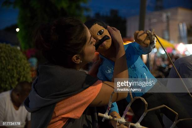 A woman kisses a figure representing Joaquin El Chapo Guzman before being burned during the Saturday of Glory as part of Holy Week celebration in...
