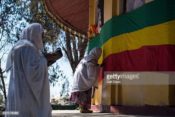 A woman kisses a large Ethiopian flag as she prays outside a church as Timkat celebrations get under way on January 18 2017 in Gondar Ethiopia Timkat...