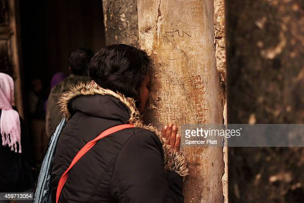 A woman kisses a pillar at the Holy Sepulchre kiss on November 29 2014 in Jerusalem IsraelThe church is said to be where Jesus was crucified and...