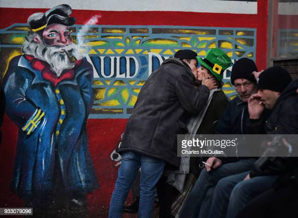 A woman kisses a stranger in the street in Temple Bar after the annual Saint Patrick's day parade takes place on March 17 2018 in Dublin Ireland...