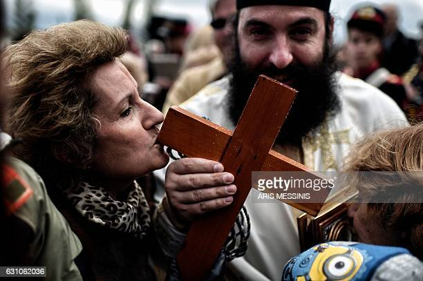 A woman kisses a wooden cross during a ceremony marking the orthodox Epiphany Day in a southern suburb of Athens on January 6 2017 / AFP / ARIS...