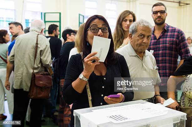 A woman kisses her ballot before casting her vote on September 27 2015 in Barcelona Spain The main Catalanist parties Catalan Democratic Convergence...