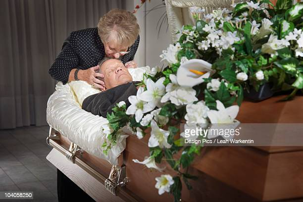 woman kisses her deceased spouse in a coffin - dead body stock-fotos und bilder