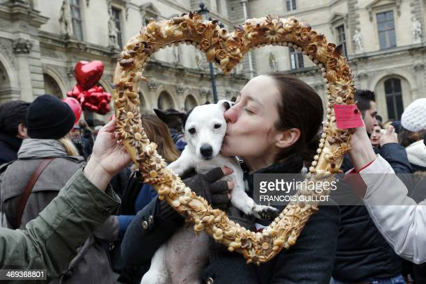 A woman kisses her dog while posing behind a heartshaped pastry during a flashmob in Paris on February 14 to mark the launch of the website...