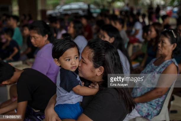 A woman kisses her son while attending Sunday mass at an evacuation center for residents who fled Taal Volcano's eruption on January 19 2020 in Lipa...