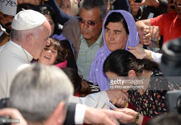 Woman kisses the hand of Pope Francis and gives him a piece of paper as he greets migrants and refugees at the Moria refugee camp on April 16, 2016...
