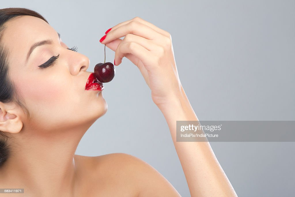 Woman kissing a cherry : Stock Photo
