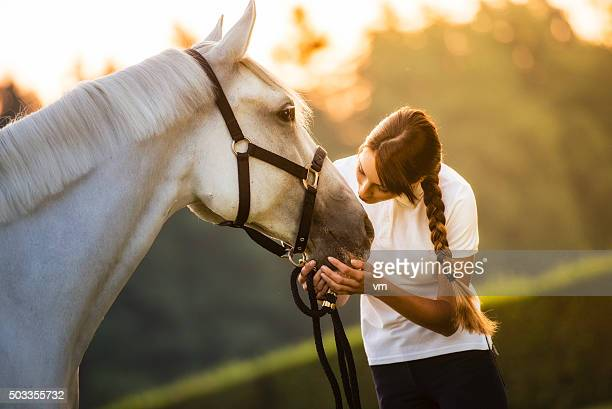 woman kissing a horse on the head in nature - aaien stockfoto's en -beelden