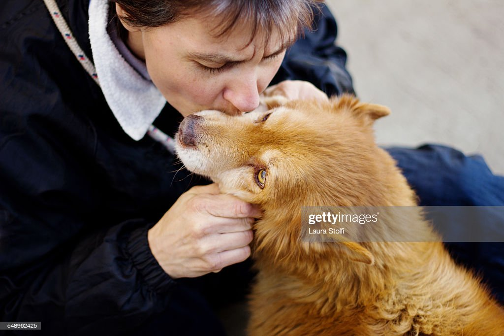 Woman kissing a little ginger dog on muzzle : Stock Photo
