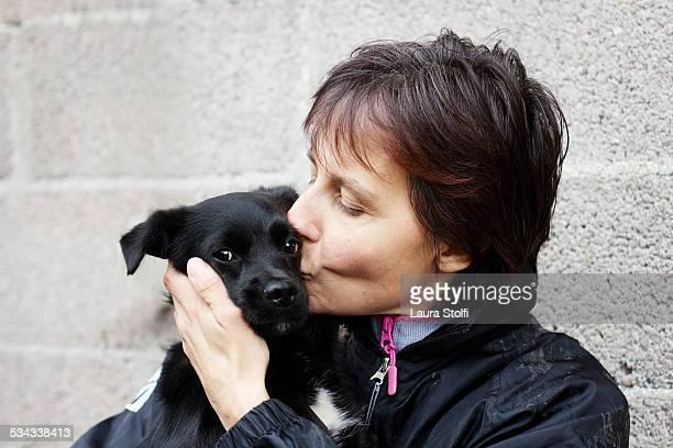 Woman kissing a looking at camera puppy dog
