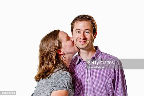 A Woman Kissing A Man On The Cheek