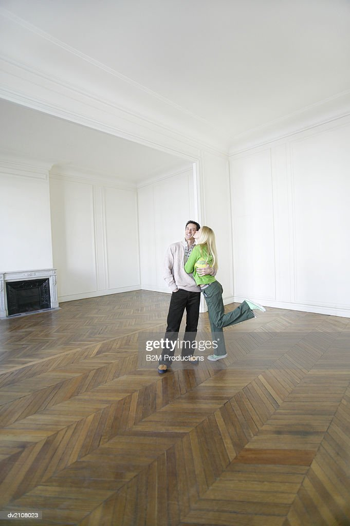 Woman Kissing a Man's Cheek in a Large Empty Room : Stock Photo