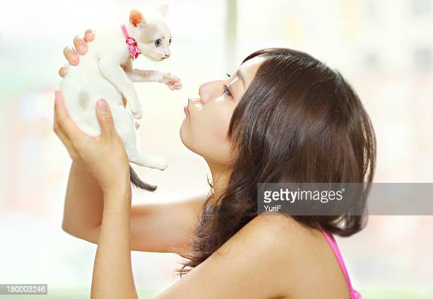 Woman kissing a white kitten