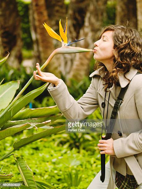 Woman kissing bird of paradise flower