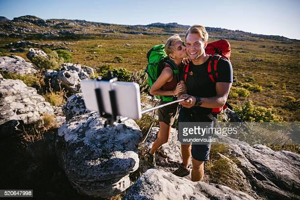 Woman kissing boyfriend on cheek for selfie on hiking vacation