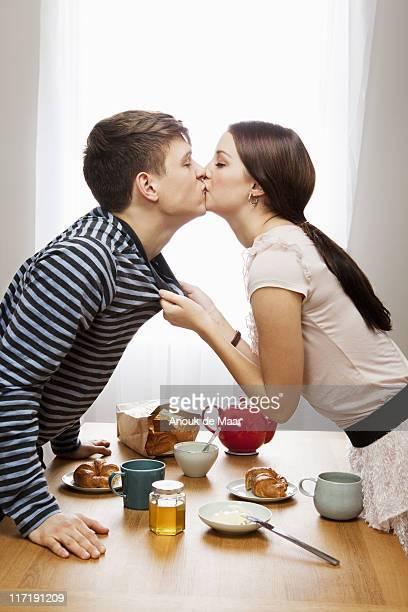 Woman kissing boyfriend ove table