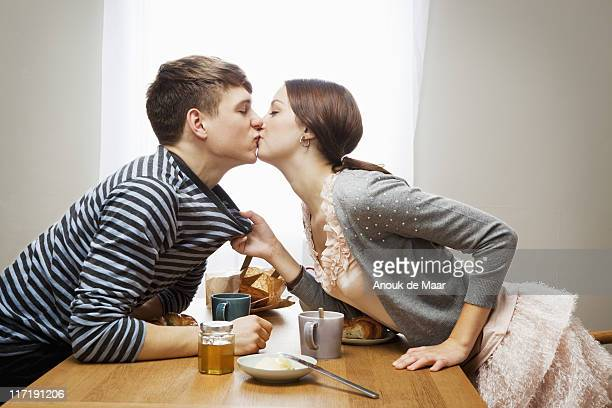 woman kissing boyfriend over table - heterosexual couple stock pictures, royalty-free photos & images
