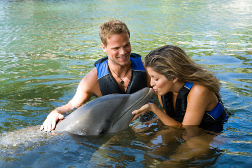 Woman kissing dolphin 57158391