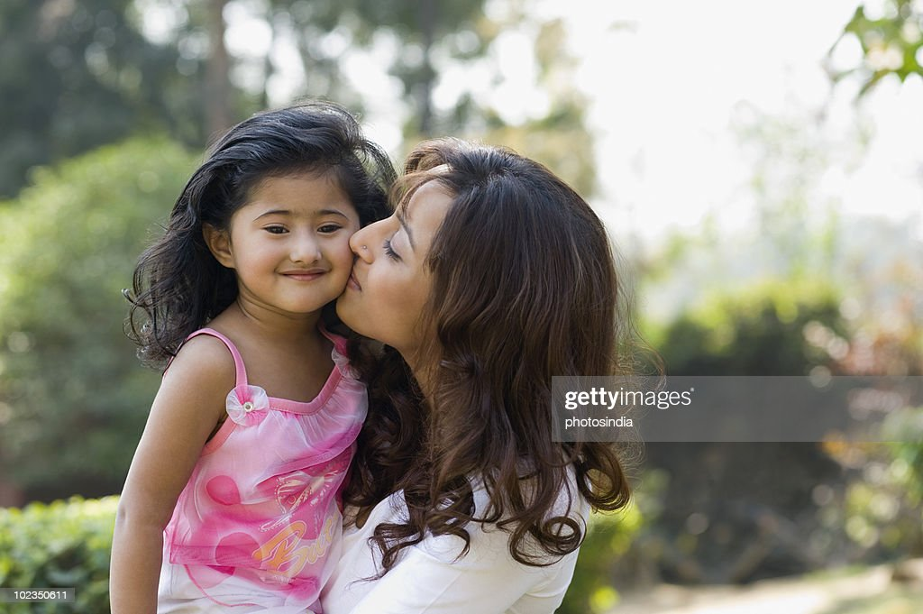 Woman kissing her daughter in a park : Stock Photo