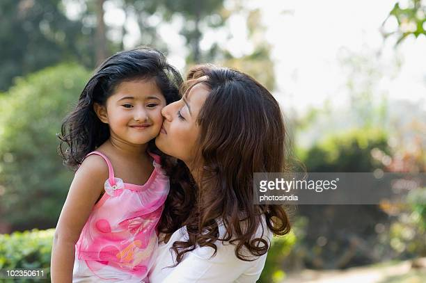 woman kissing her daughter in a park - indian girl kissing stock photos and pictures