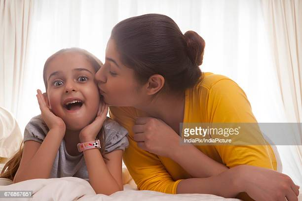 woman kissing her daughter on the bed - indian girl kissing stock photos and pictures