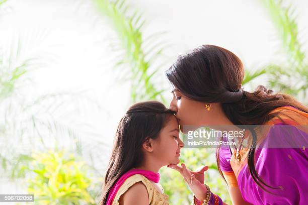 woman kissing her daughters forehead - indian girl kissing stock photos and pictures
