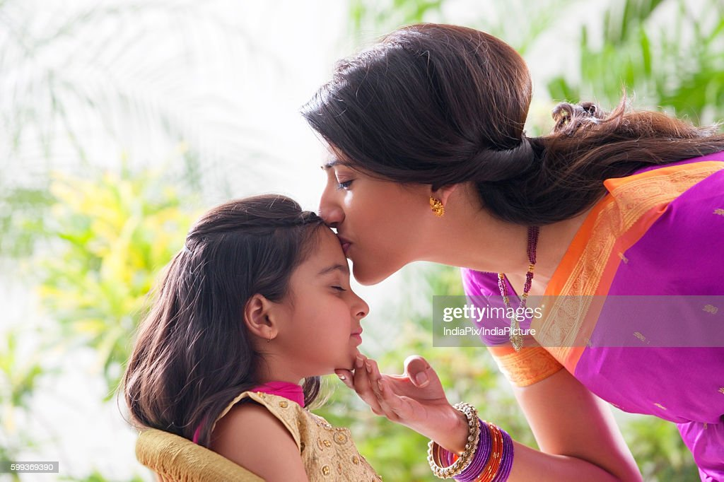 Woman kissing her daughters forehead : Foto de stock