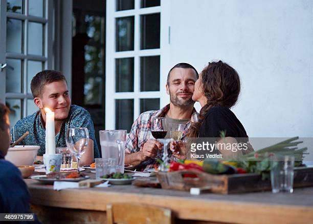 woman kissing husaband at outside dinner table - grupo pequeño de personas fotografías e imágenes de stock