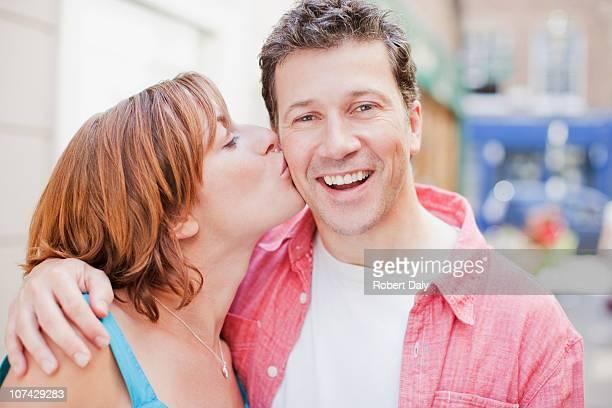 Woman kissing husbands cheek outdoors