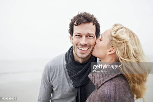 woman kissing husband's cheek - uomini di età media foto e immagini stock