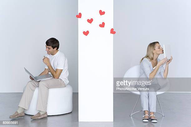woman kissing laptop computer, man looking at his own laptop and smiling, hearts in the air between them - distant stock pictures, royalty-free photos & images